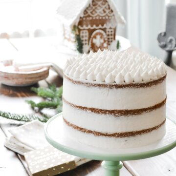 Rum raisin apple butter cake with vanilla buttercream, and a gingerbread house in the background.
