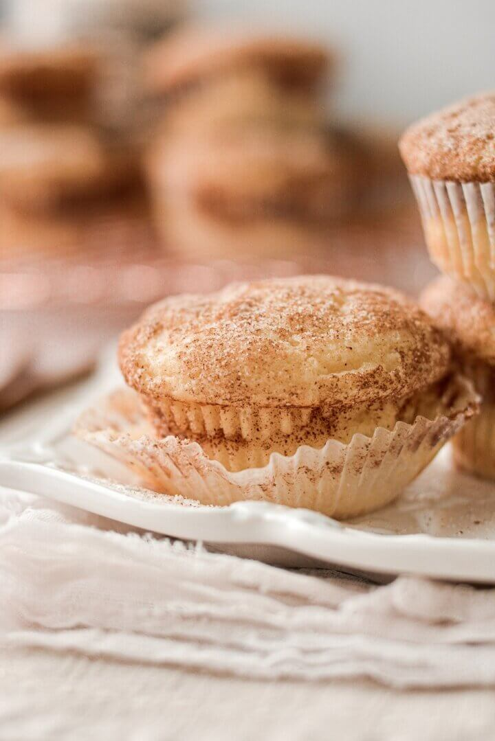 Snickerdoodle muffins stacked on a white plate.