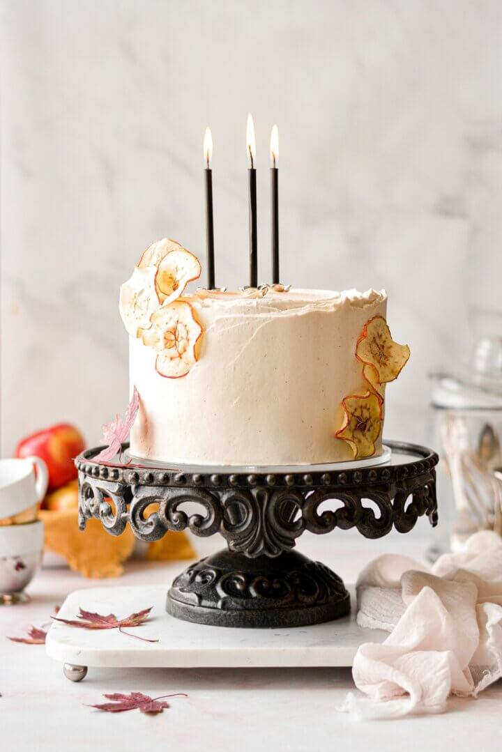 Apple cider cake with maple vanilla bean buttercream, with dried apples garnish and black candles.