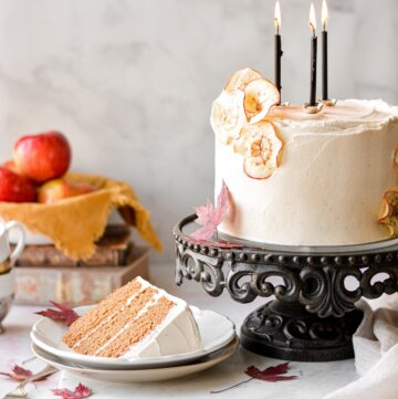 Apple cider cake with maple vanilla bean buttercream, with one slice cut.