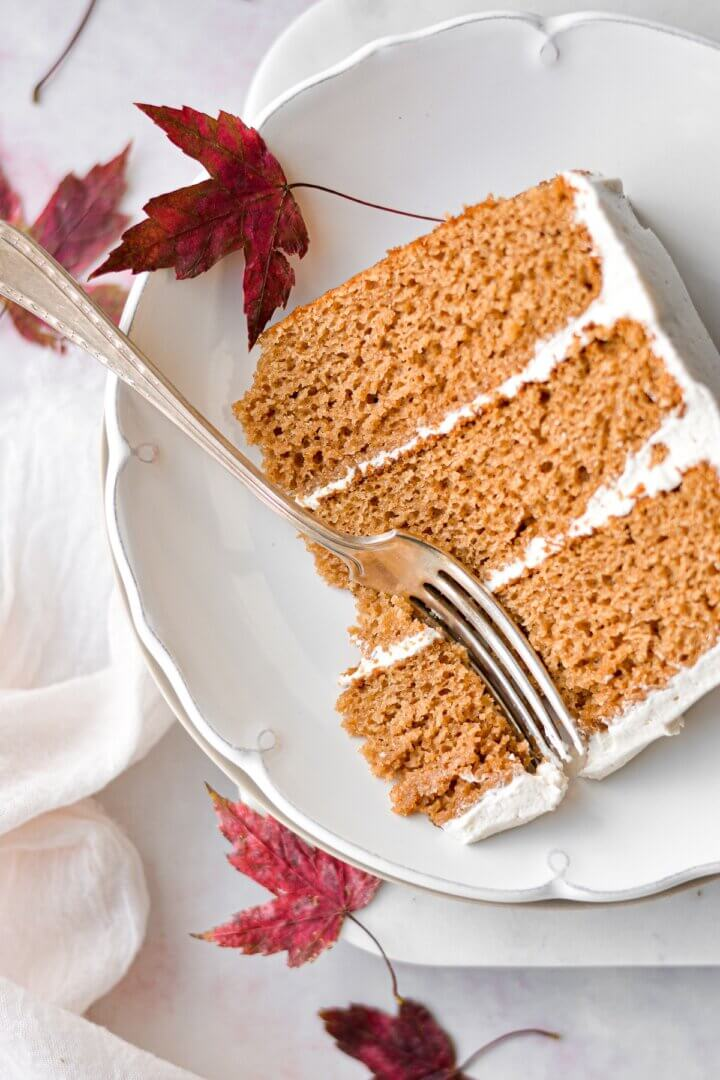 A slice of apple cider cake with maple buttercream, surrounded by dried maple leaves.