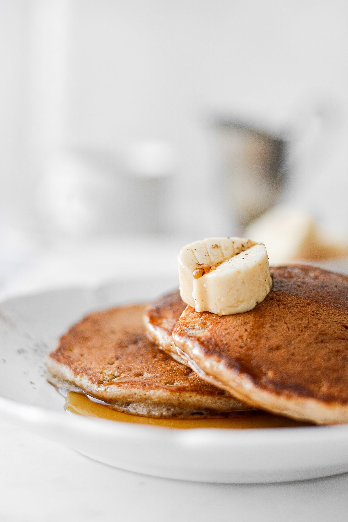 Apple cider pancakes with maple syrup and a butter leaf.