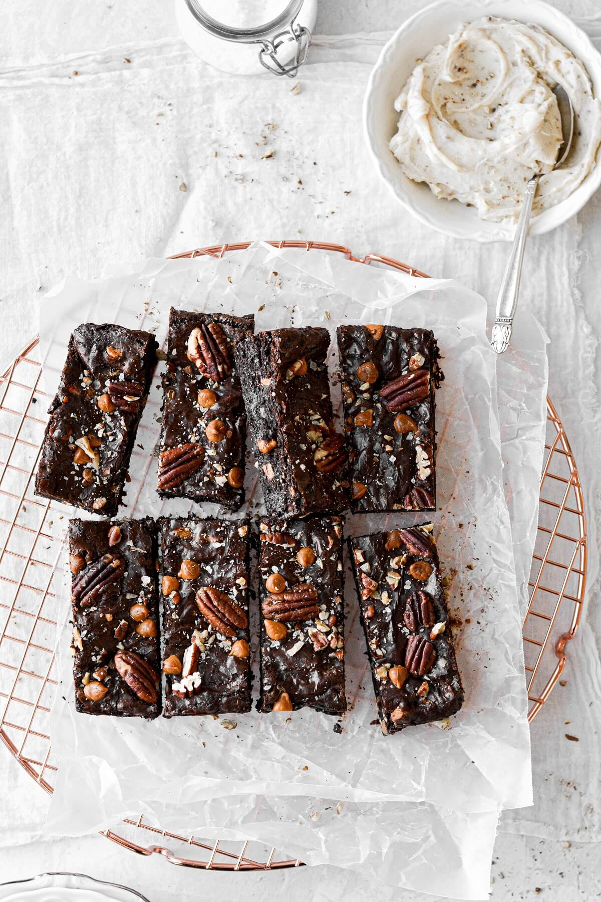 Butter pecan brownies with brown butter pecan frosting, on a copper cooling rack.