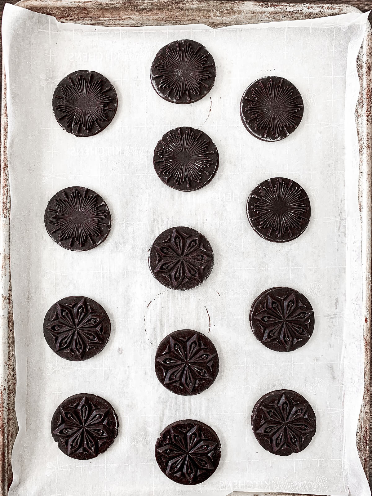 Unbaked stamped chocolate shortbread cookies on a baking sheet.