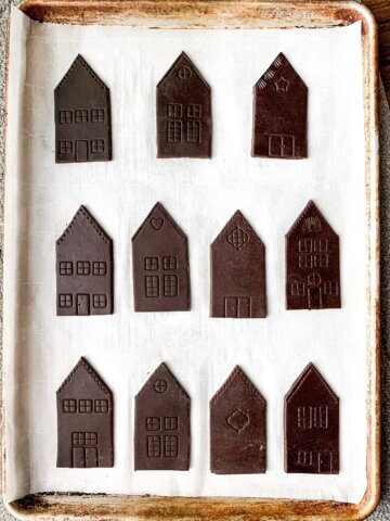 A tray of unbaked chocolate sugar cookie houses.