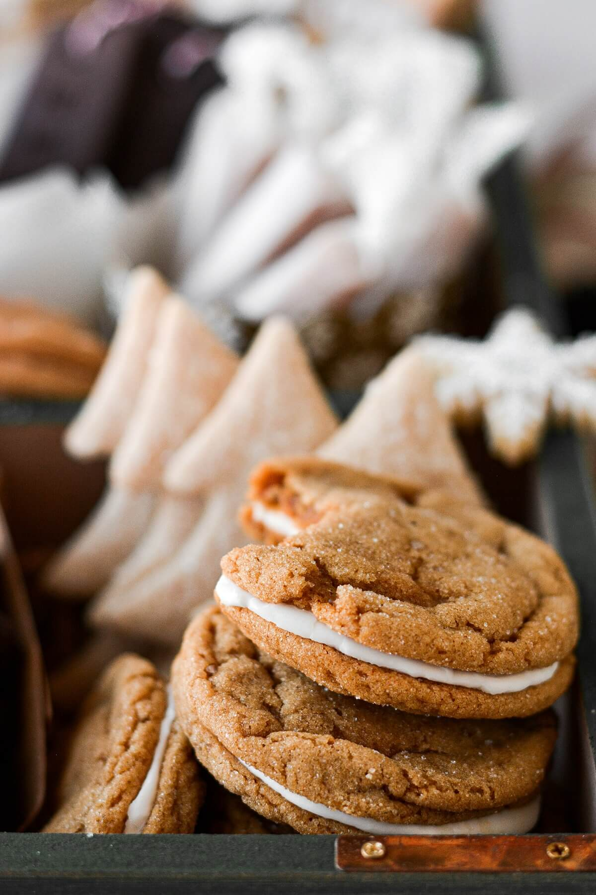 Ginger molasses lemon sandwich cookies in a box of Christmas cookies.
