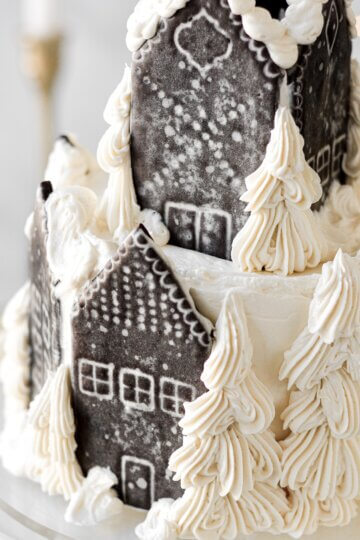 Gingerbread village Christmas house, decorated with chocolate sugar cookie houses and buttercream trees.
