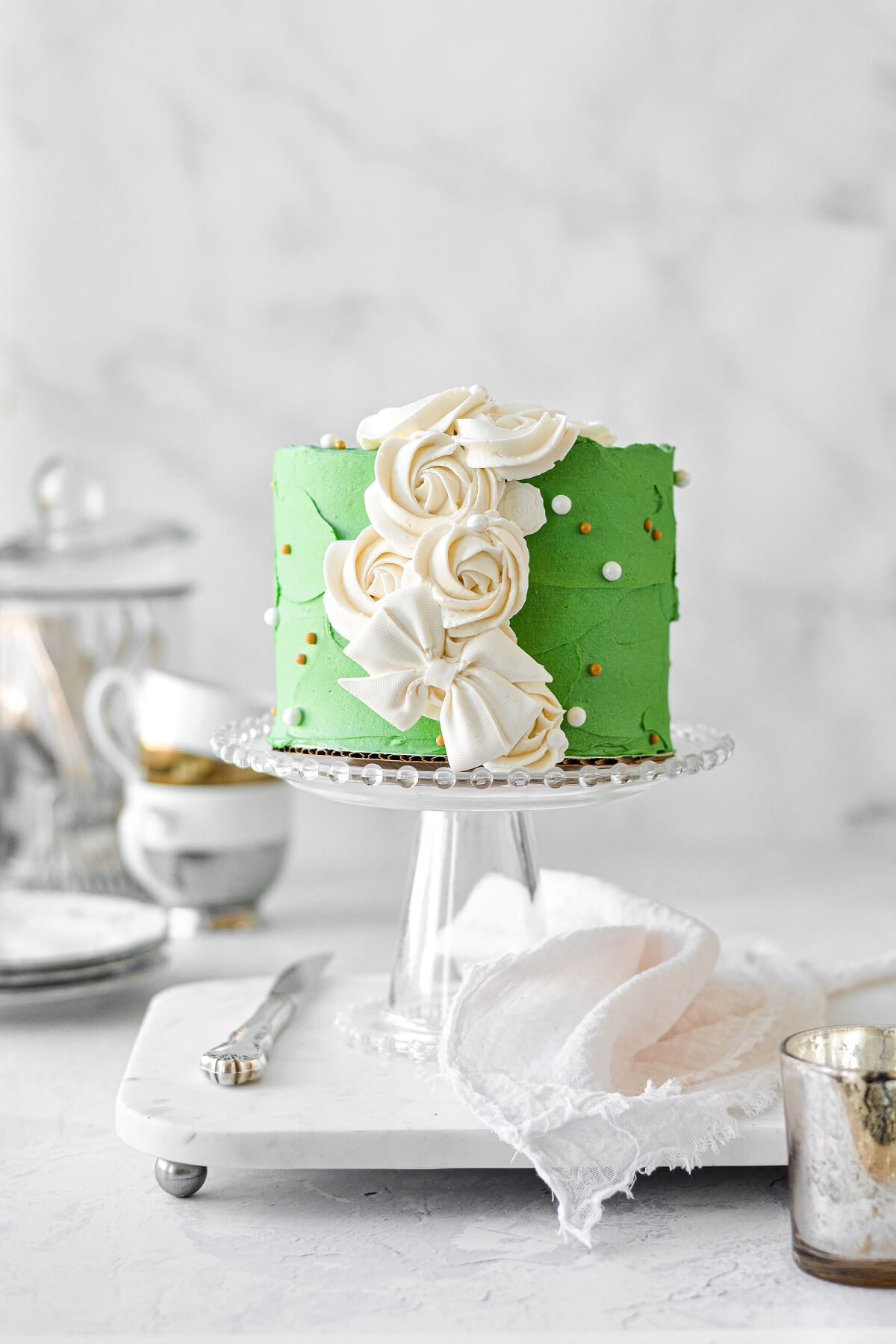 A Christmas cake with green buttercream, white rosettes and a white chocolate bow.