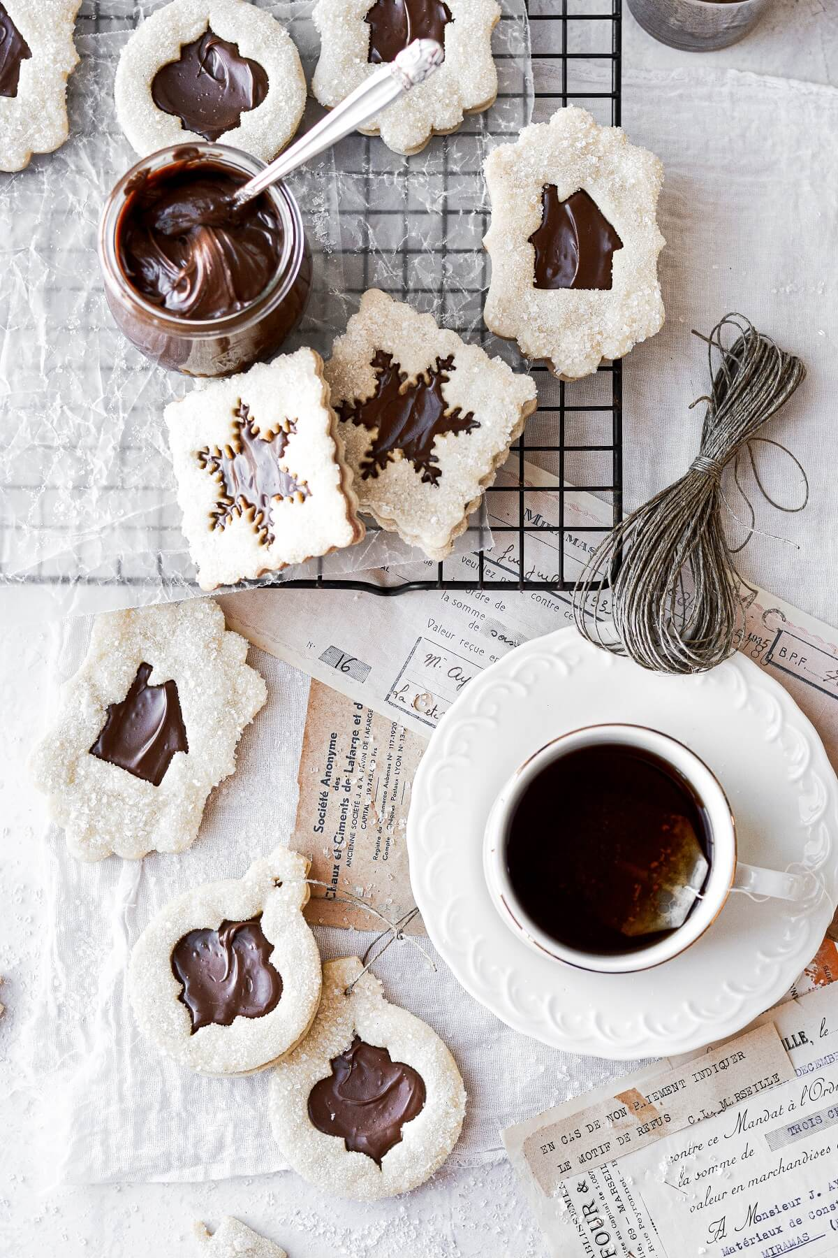 Chocolate hazelnut linzer cookies, scattered around a cup of hot tea.