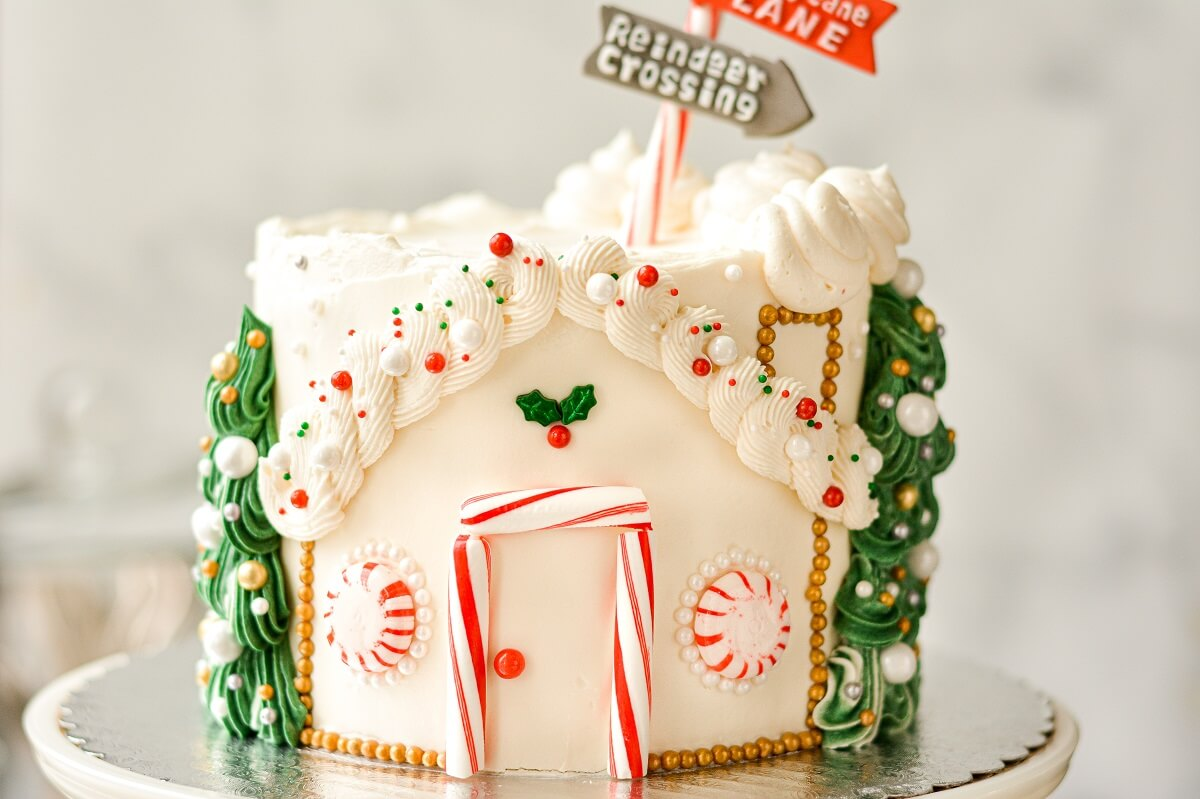 A Christmas cake decorated like Santa's workshop, and topped with a candy cane street sign.