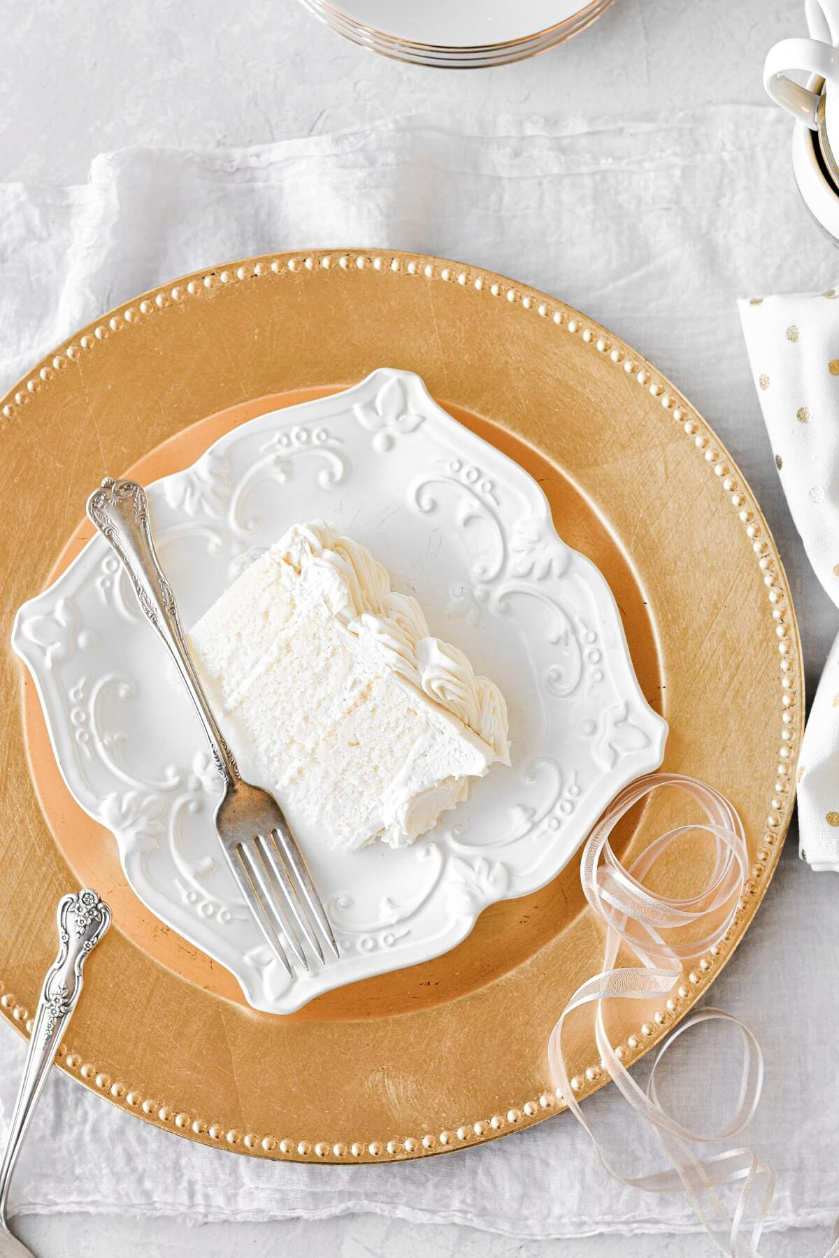 A slice of white velvet cake on a gold charger plate.