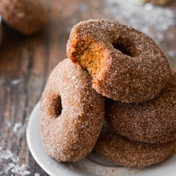 A stack of baked gingerbread doughnuts, one with a bite taken out of it.