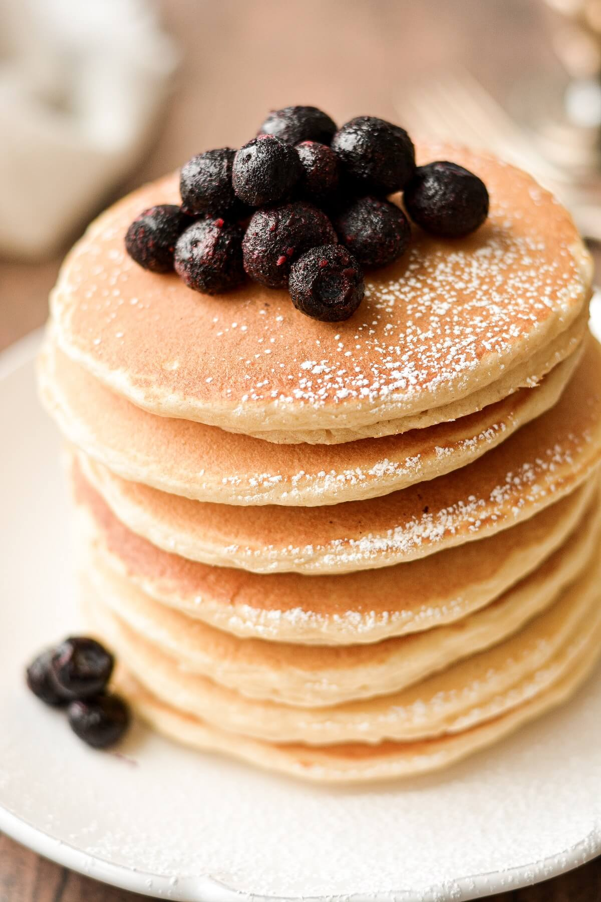 A stack of the best classic pancakes, topped with blueberries.