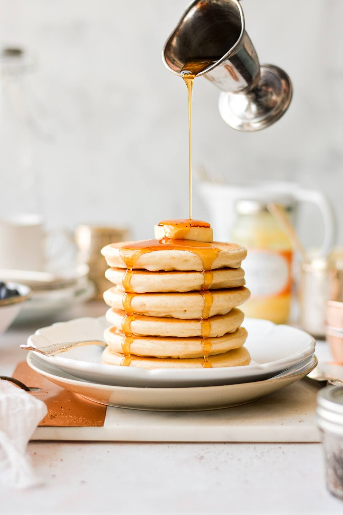A stack of classic fluffy pancakes, with syrup pouring on top.