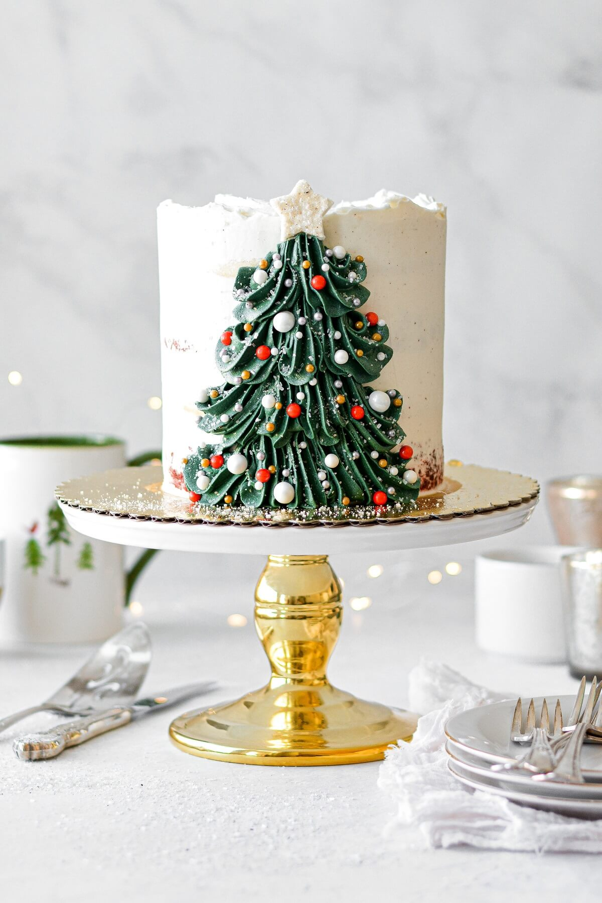 A Christmas tree cake with a buttercream Christmas tree decorated with sprinkle ornaments and a sugar star.