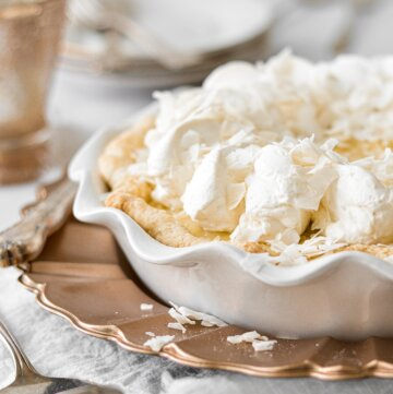 Coconut cream pie on a gold charger plate.