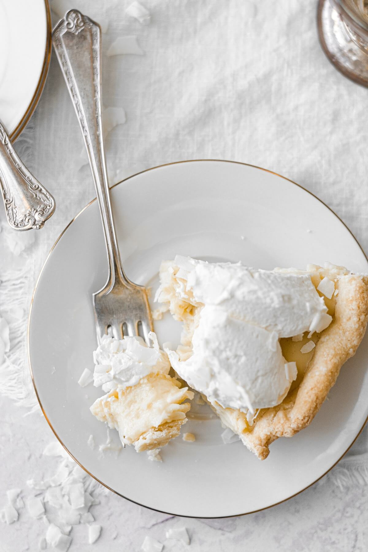 A slice of coconut cream pie with a bite taken.