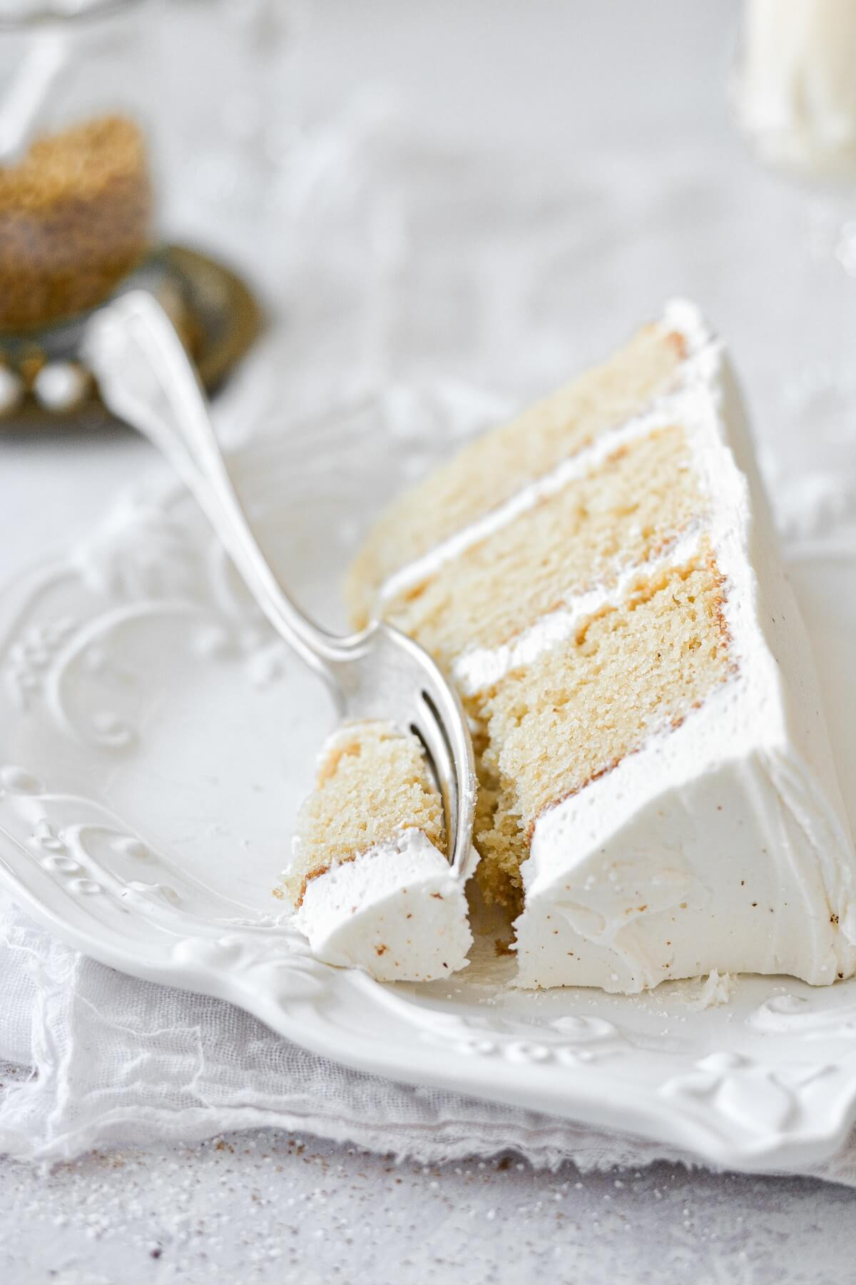 A slice of eggnog cake on a white plate.