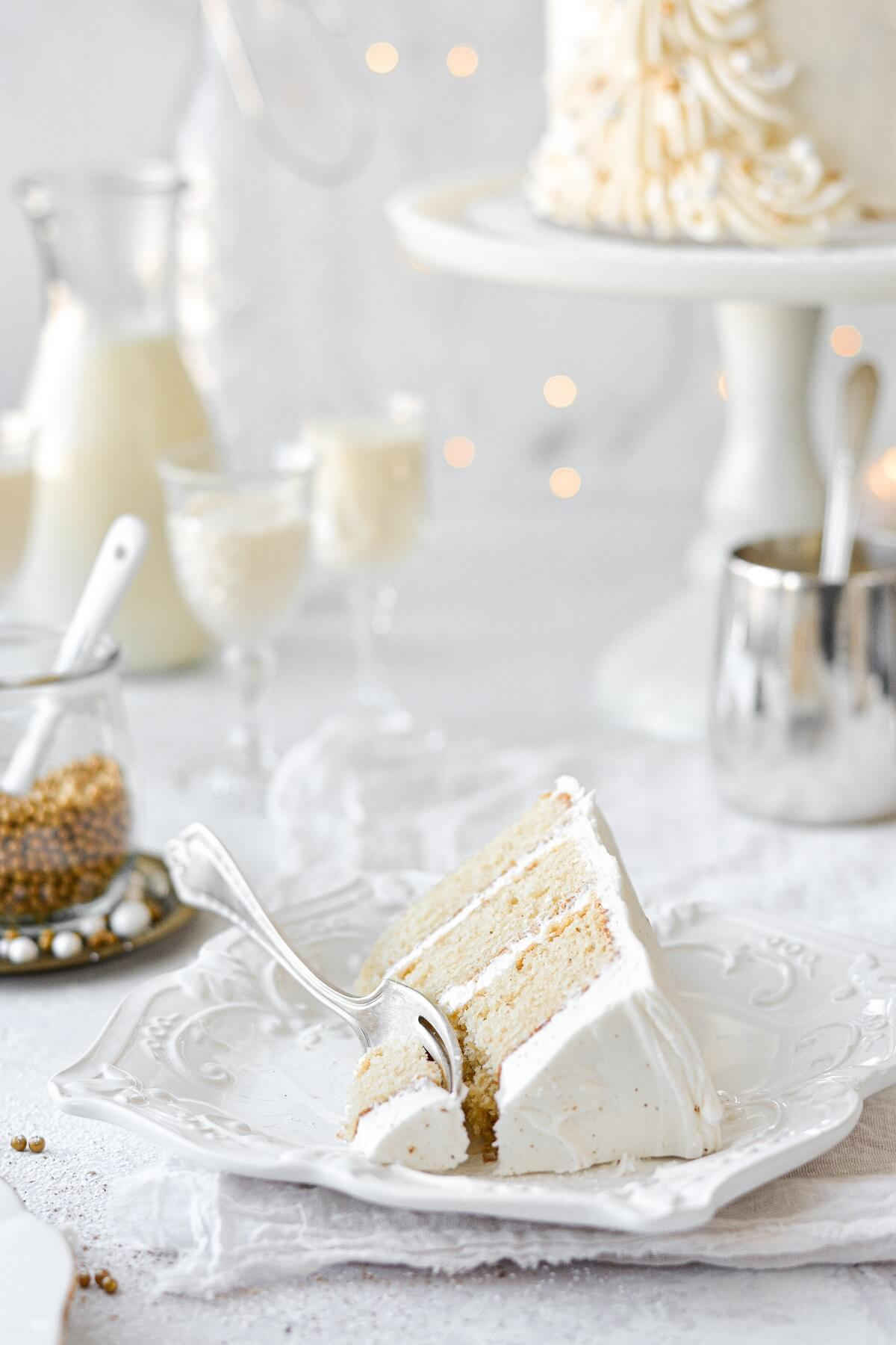 A slice of eggnog cake, with glasses of eggnog in the background.