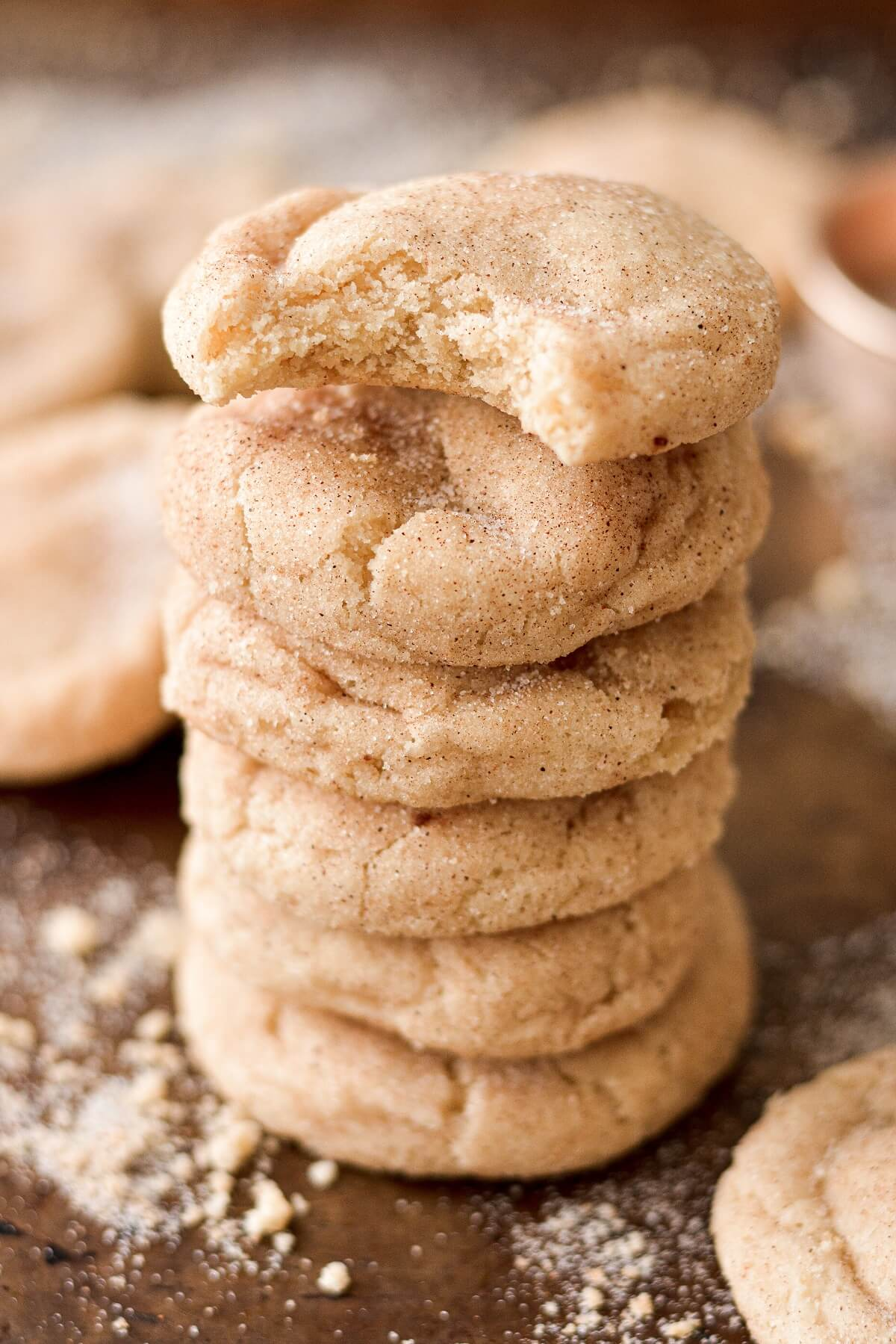 A stack of high alititude snickerdoodles, one with a bite taken out of it.