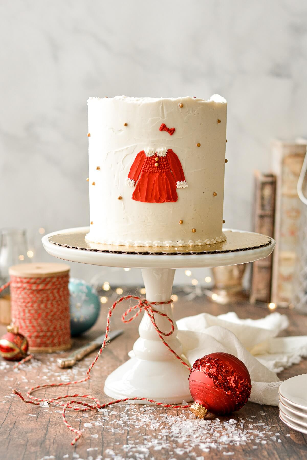 A Christmas cake with gold and red sugar pearls, ornaments, and a red Christmas dress painted on the cake in buttercream.