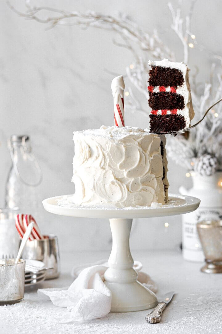 North Pole cake, with a slice being lifted up, showing red and white striped buttercream inside.