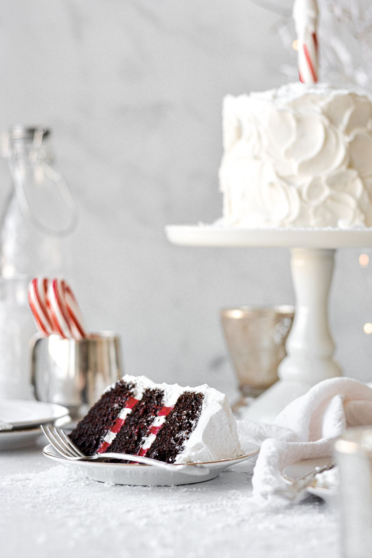 A slice of chocolate cake, with red and white striped buttercream, and a candy cane North Pole on top.