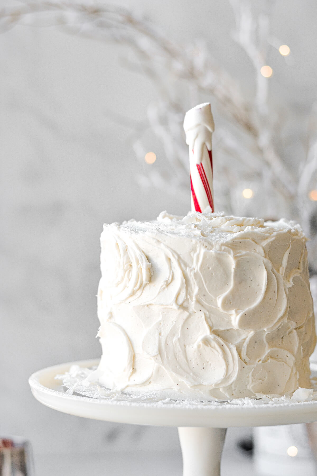 A layer cake with swirls of vanilla buttercream, and a candy cane North Pole on top.