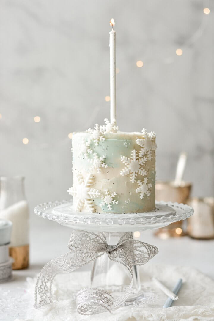 Light blue and white snowflake cake with a white birthday candle.