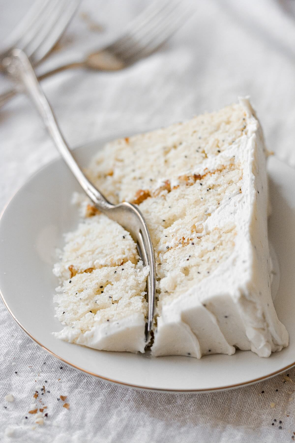 A slice of almond poppyseed cake with a bite cut.