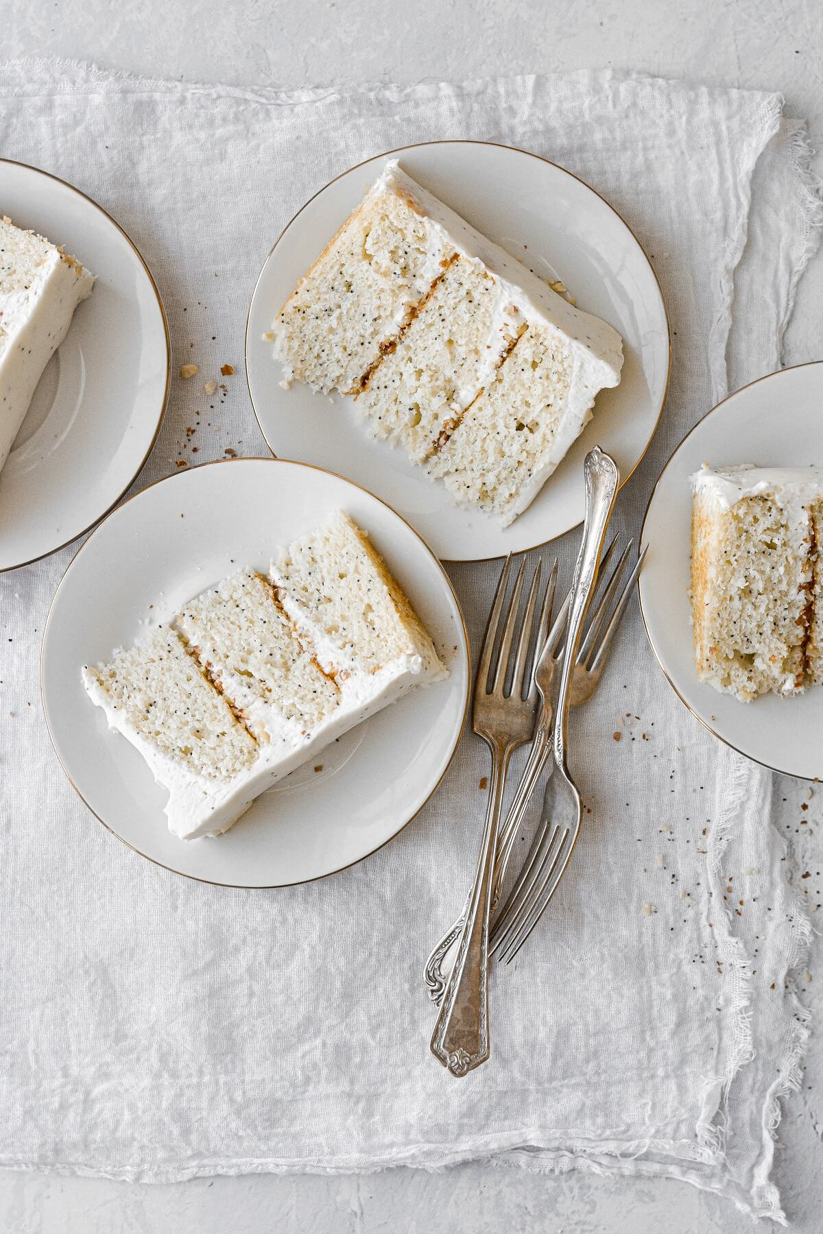 Slices of almond poppyseed cake on white plates.