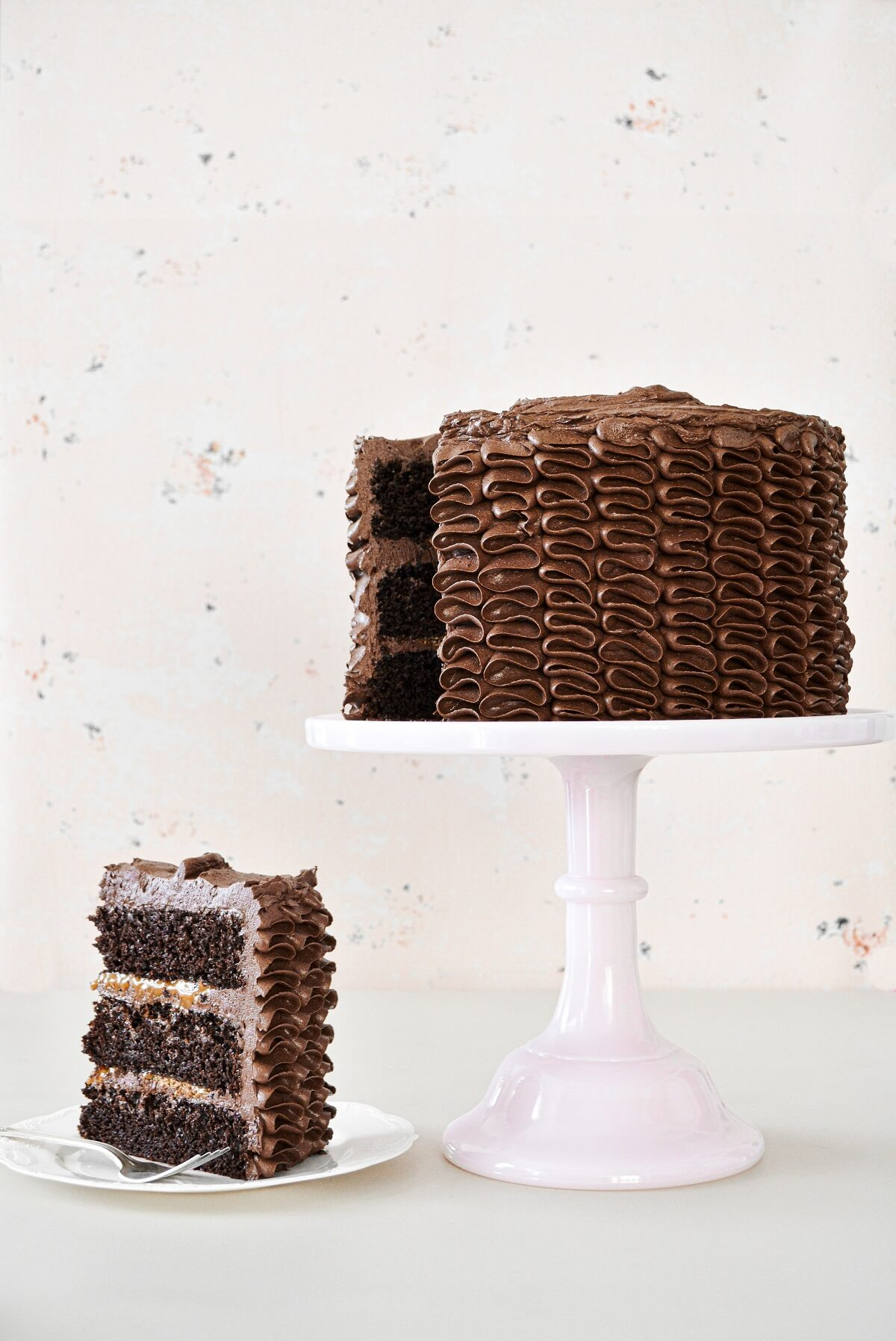 Chocolate caramel toffee cake with piped ruffled buttercream, and a slice cut.