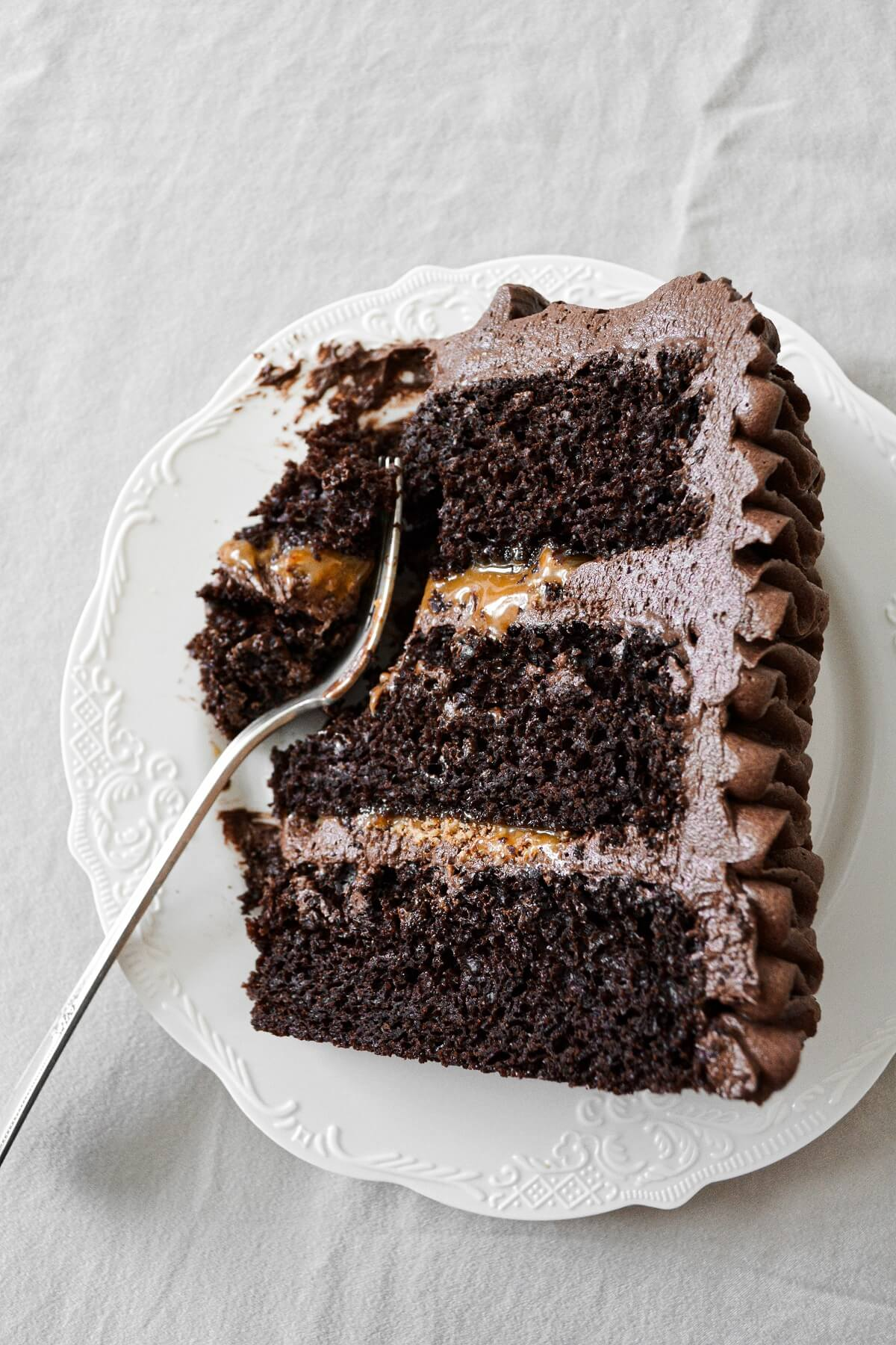 A slice of chocolate caramel toffee cake with piped ruffled buttercream.