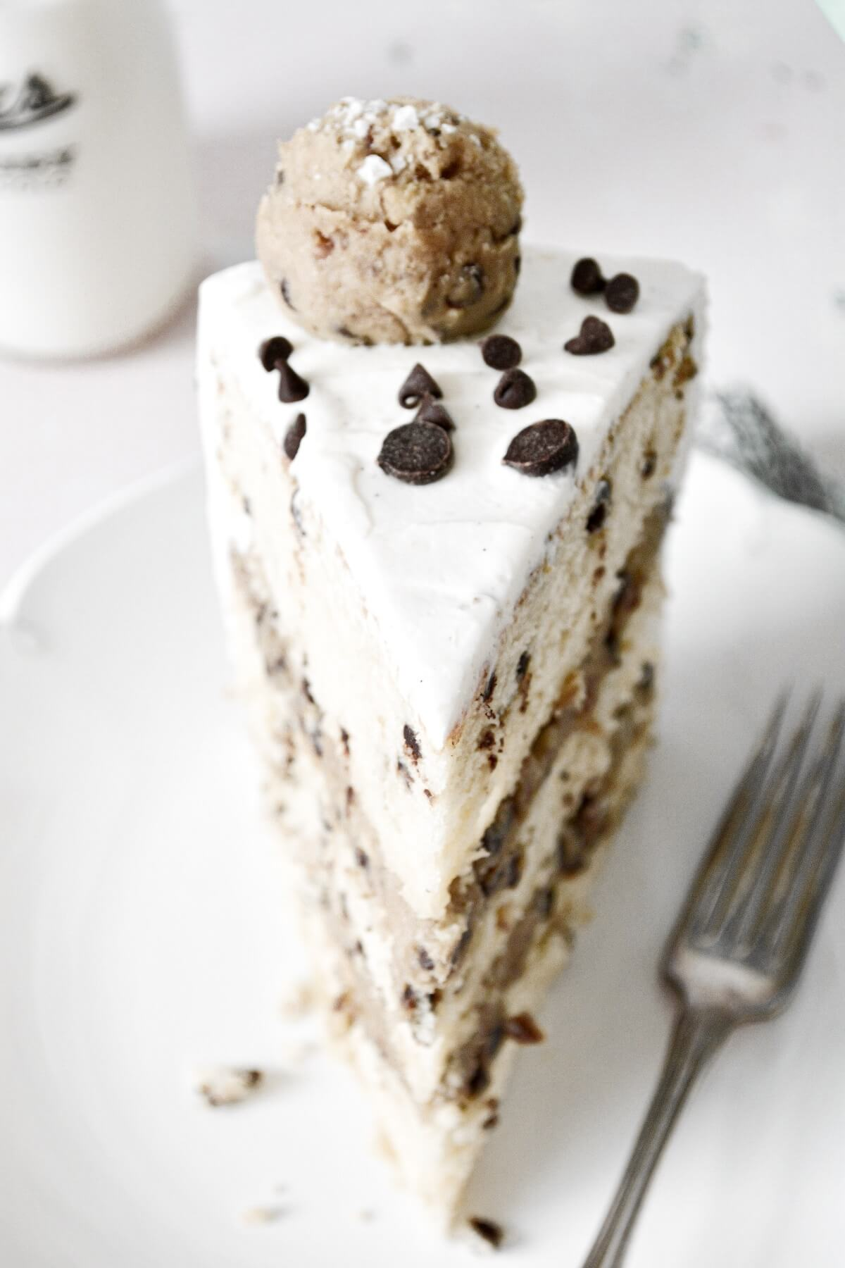 A slice of chocolate chip cookie dough cake, decorated with chocolate chips and balls of cookie dough.