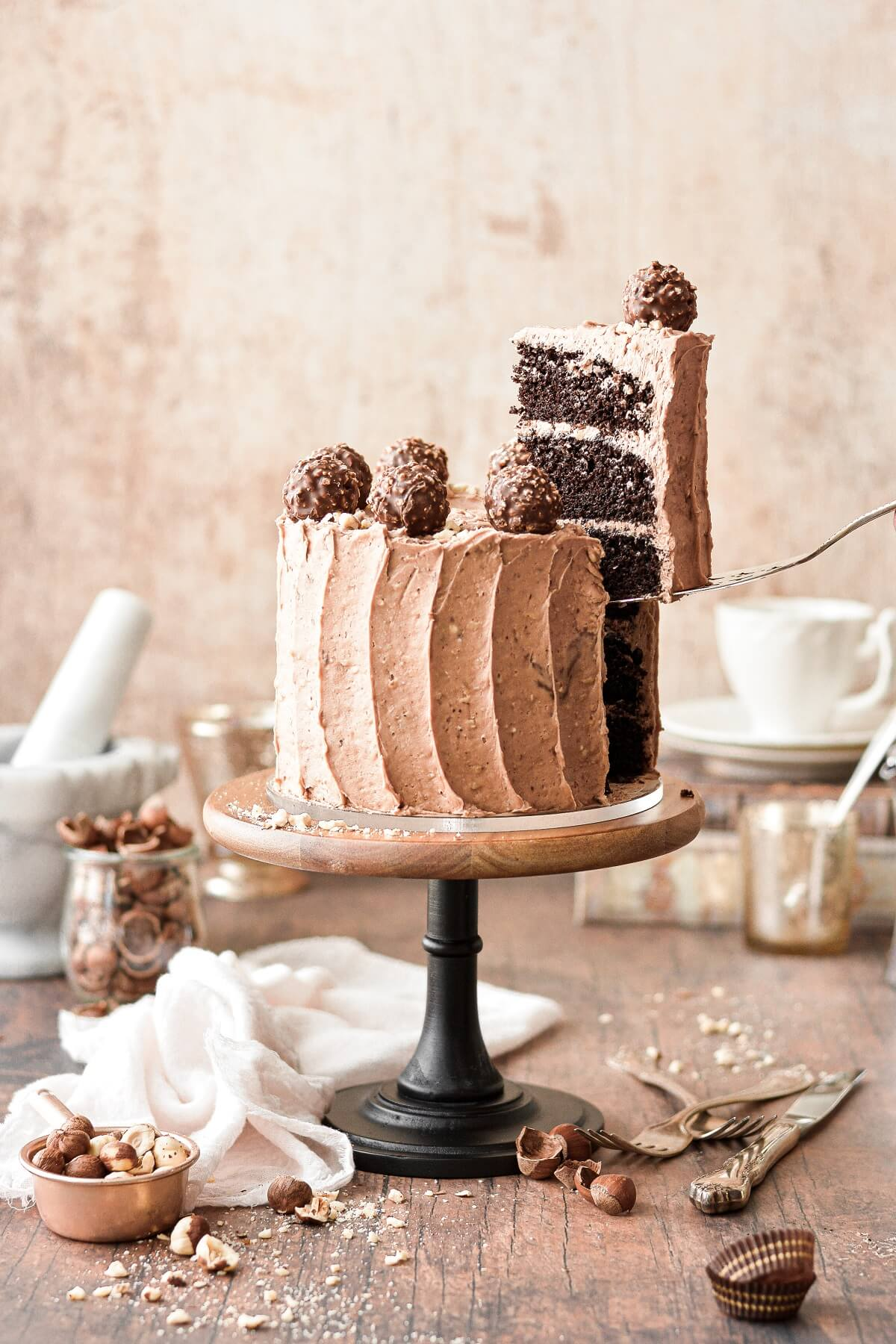Chocolate hazelnut cake with a slice being lifted out.
