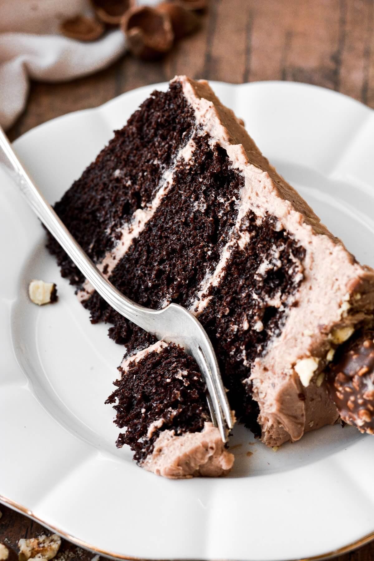 A slice of chocolate hazelnut cake with a bite taken.