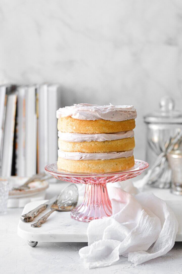 Naked vanilla cake with blush buttercream on a pink cake stand.