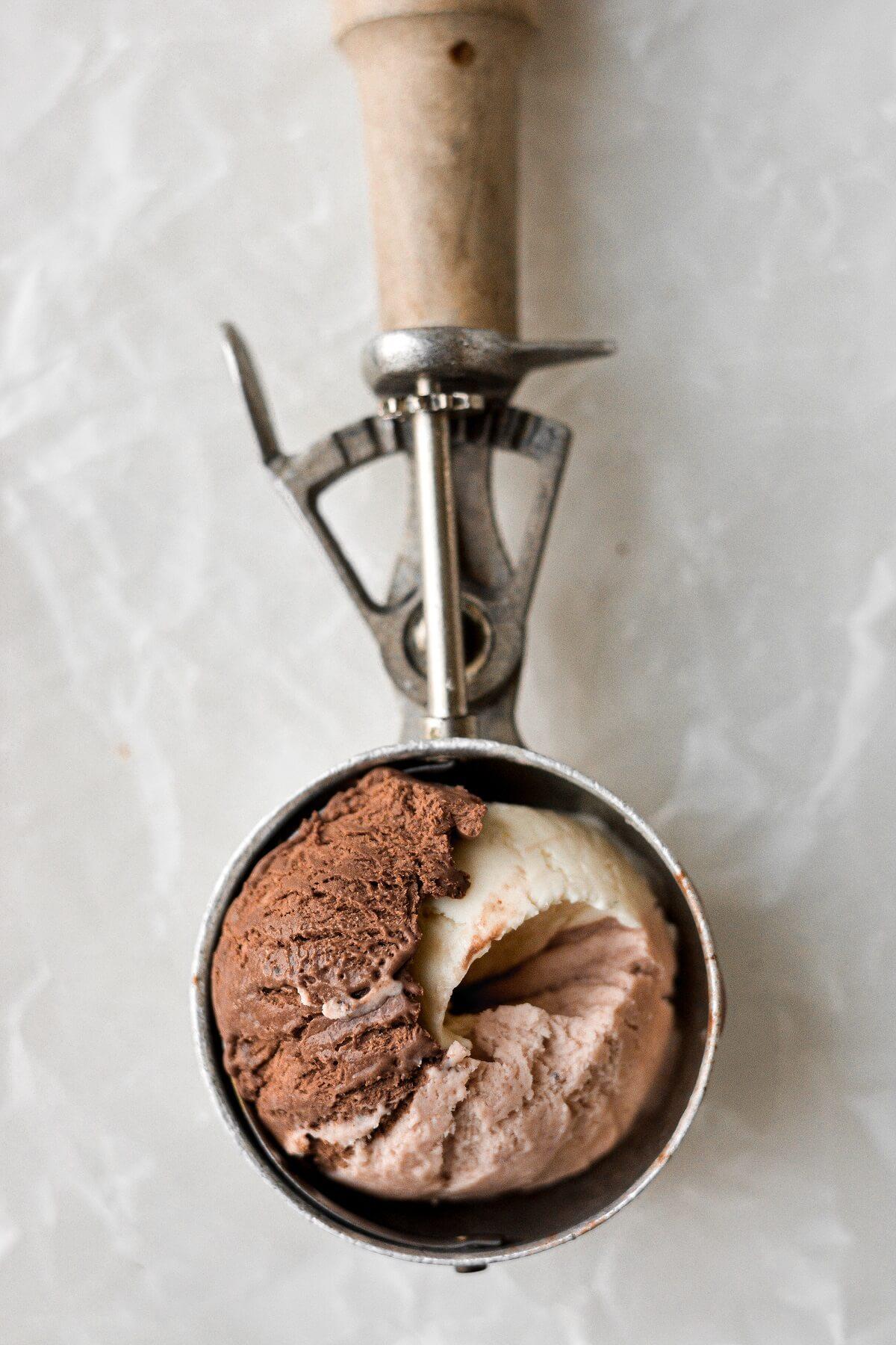 A scoop of neapolitan no churn ice cream in a vintage ice cream scoop.