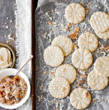 Ginger shortbread cookies with orange icing, scattered on a baking sheet.