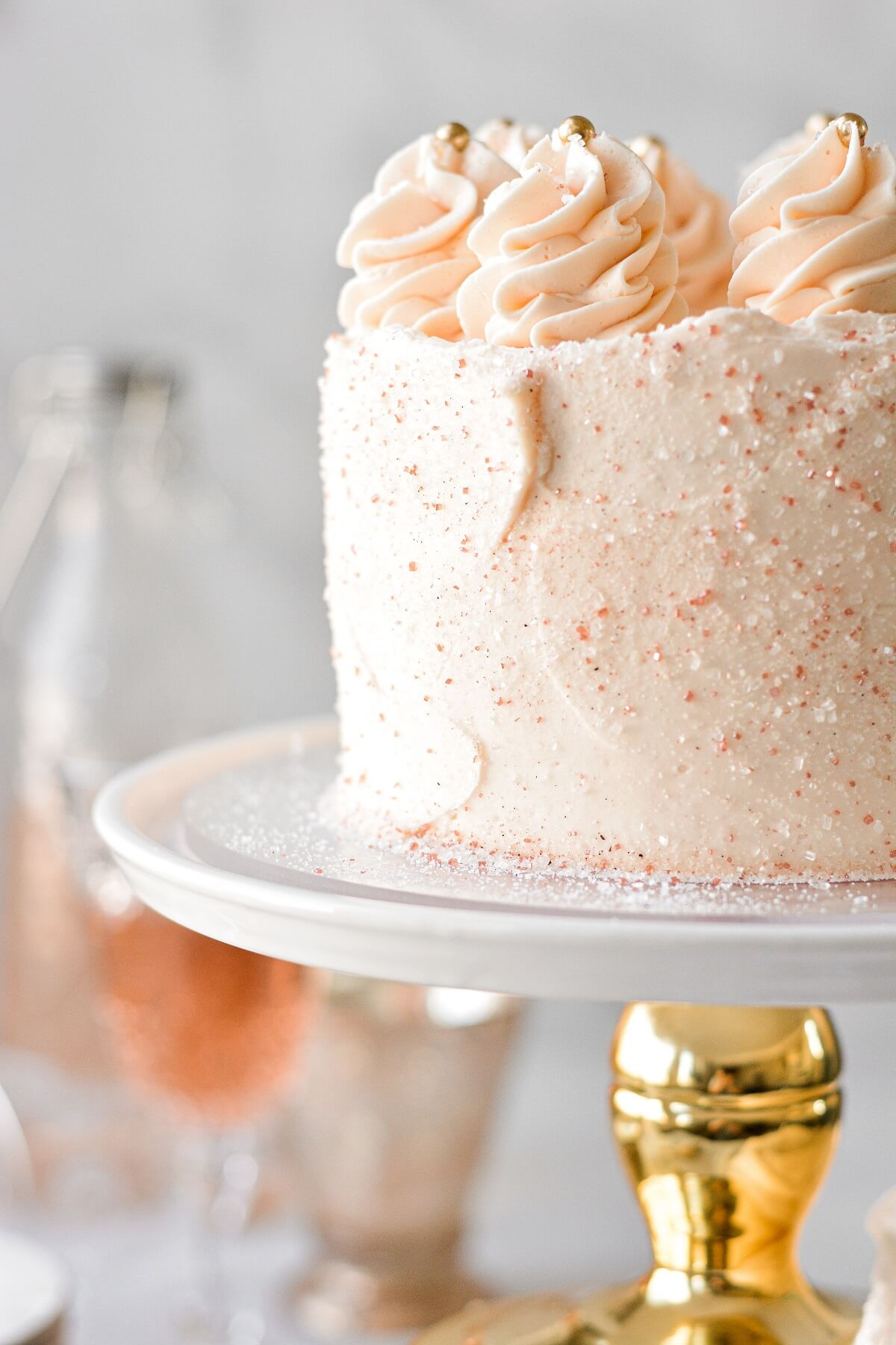 Pink champagne cake with sparkling sugar and piped swirls of buttercream.