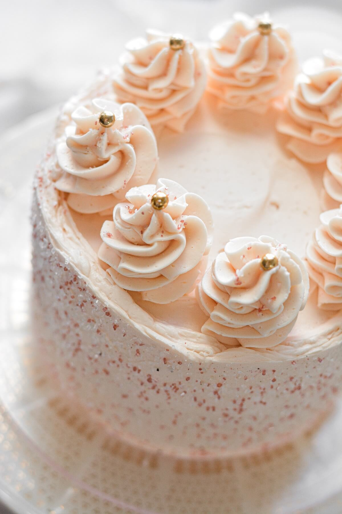 Pink champagne cake with sparkling sugar, piped swirls of buttercream, and gold sugar pearls.