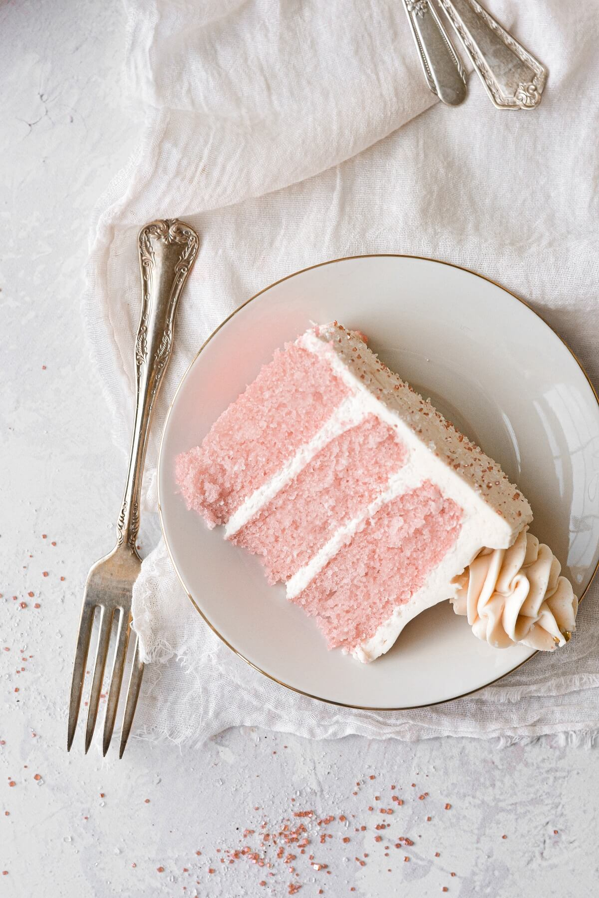 A slice of pink champagne cake with sparkling sugar.