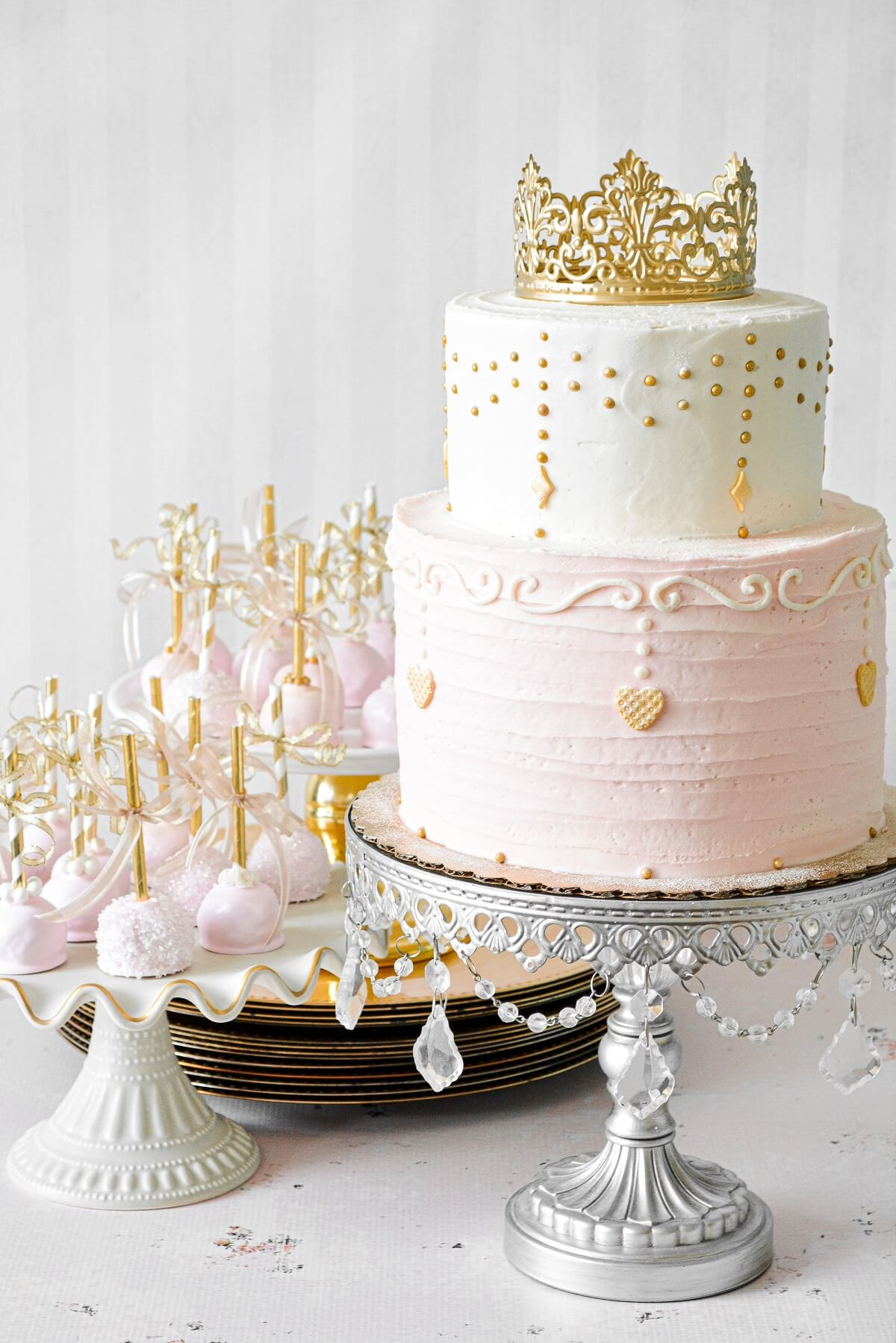 Pink and gold princess party cake with a gold crown topper.
