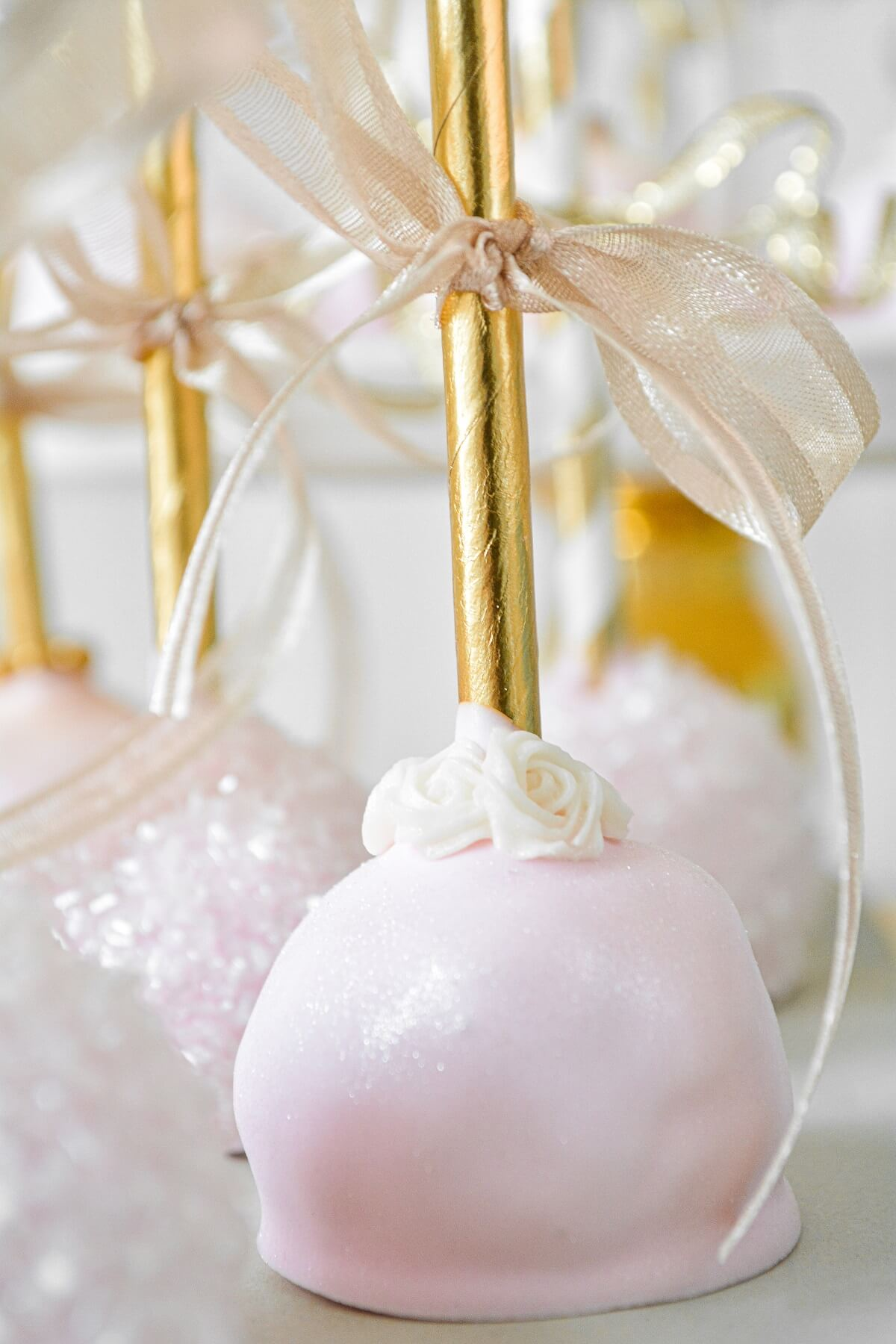 Pink and gold princess party cake pops with gold ribbons.