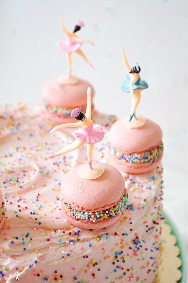 A pink sprinkles cake with French macarons and ballerina cake toppers.