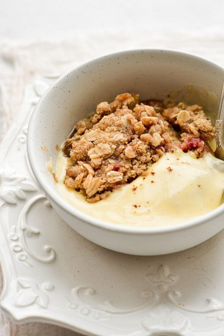 A bowl of rhubarb crumble, served with vanilla bean custard.