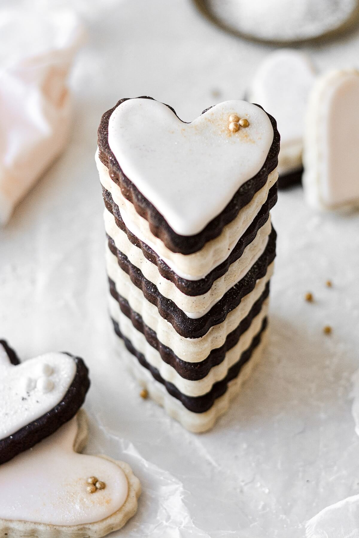 A stack of heart shaped chocolate and vanilla sugar cookies, frosted with pale pink royal icing.