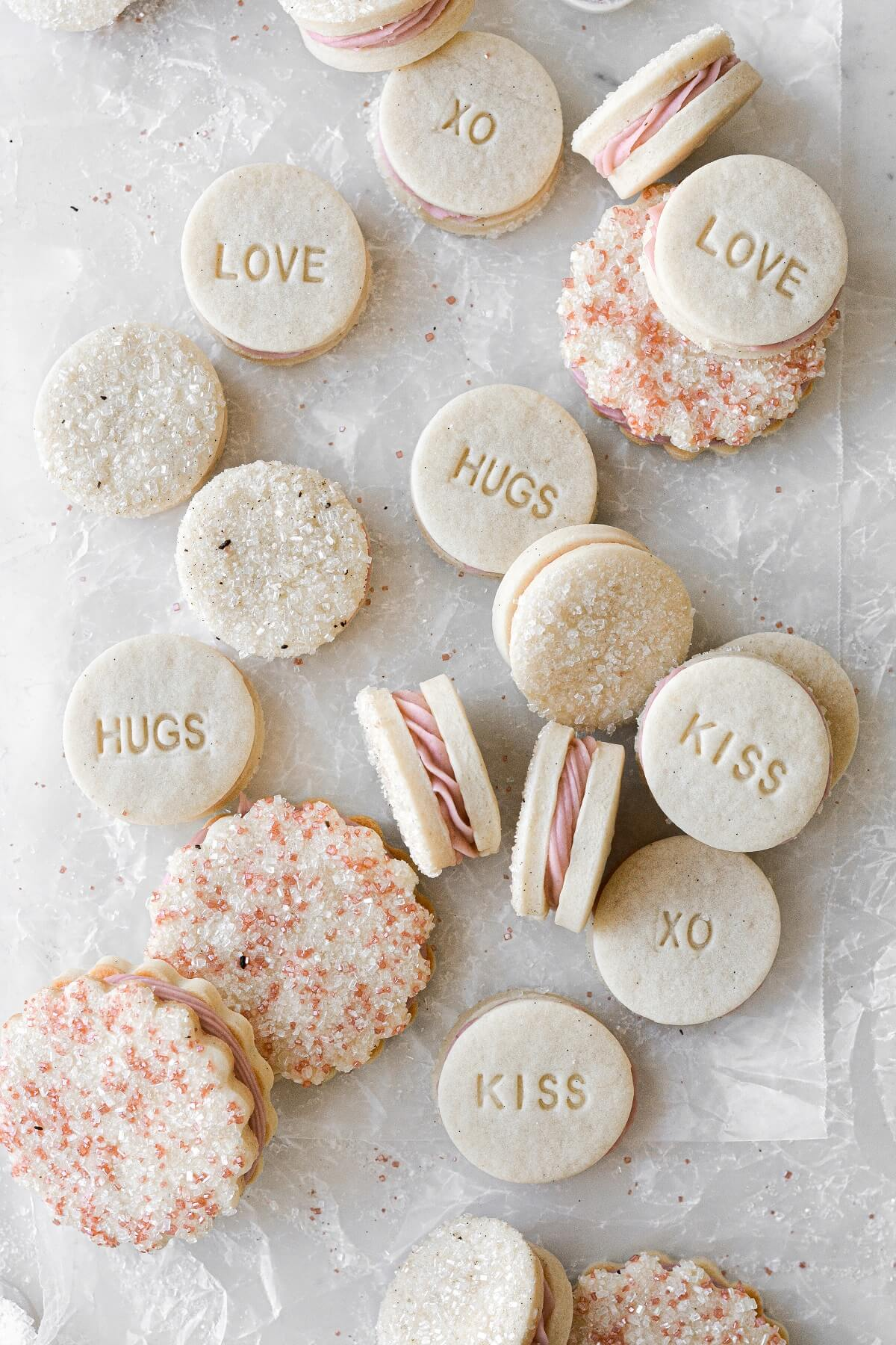 """Vanilla raspberry sandwich cookies, some with sparkling sugar and some stamped """"xo"""", """"hugs"""", """"kiss"""", and """"love"""".."""