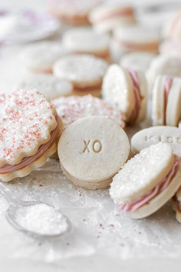 """Vanilla raspberry sandwich cookies, with sparkling sugar and stamped """"xo""""."""