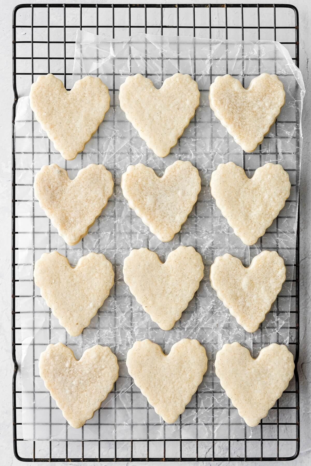 Heart shaped vanilla bean sugar cookies on a black cooling rack.